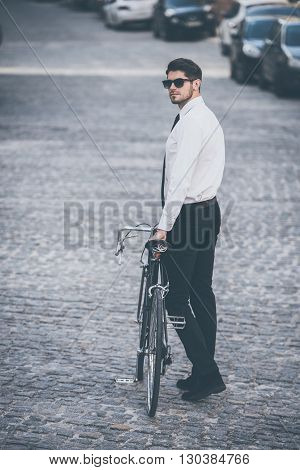 Fashion on a go. Full-length rear view of handsome well-dressed young man rolling his bicycle outdoors