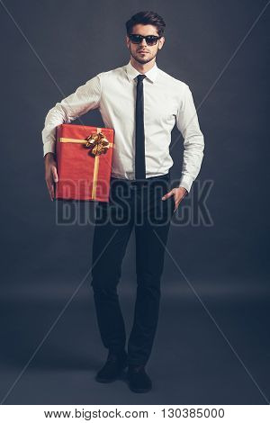 Surprise for you. Full length of handsome well-dressed young man holding gift box and looking at camera while standing against grey background