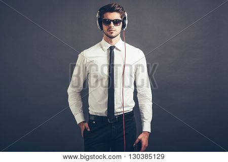 Music is his style. Handsome well-dressed young man in headphones looking at camera while standing against grey background