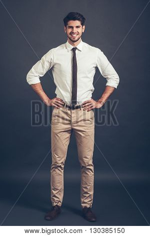 Keep smiling. Full length of confident young handsome man keeping arms akimbo and looking at camera with smile while standing against grey background