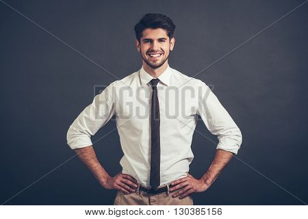 Best smile. Confident young handsome man keeping arms akimbo and looking at camera with smile while standing against grey background