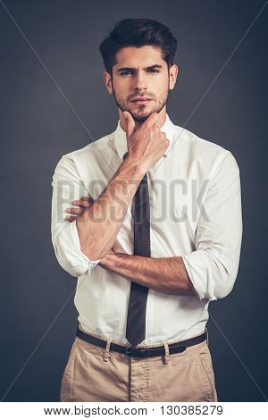 I will think about it. Confident young handsome man keeping hand on chin and looking at camera while standing against grey background