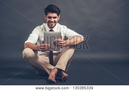 Working with pleasure. Full length of confident young handsome man using his digital tablet with smile while sitting on the floor against grey background