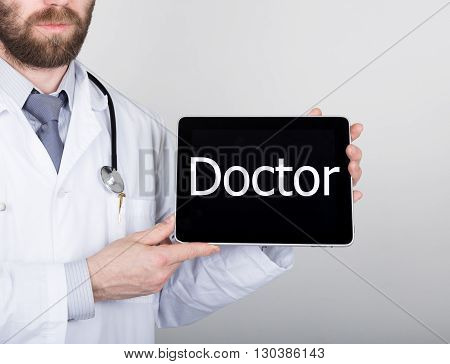technology, internet and networking in medicine concept - Doctor holding a tablet pc with doctor sign. Internet technologies in medicine.