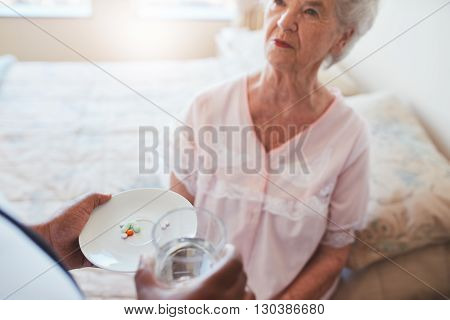 Senior woman sitting on bed and home care nurse giving medication. Hand of nurse giving pills to elderly female patient.