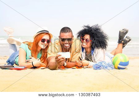 Multiracial friends having fun taking selfie lying on the beach - Happy multiethnic students watching self photo on vacation - Concept of teens joyful moment togetherness and technology addiction
