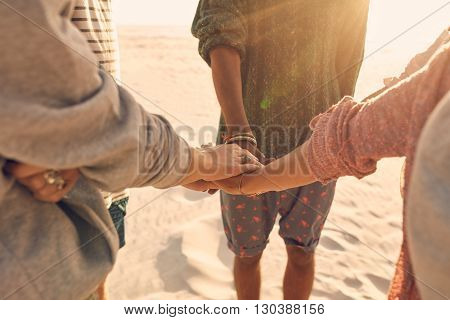 Group of friends stack their hands together. Young men and women standing together at the beach stacking their hands concept of unity and teamwork.