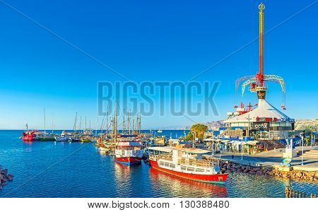 EILAT ISRAEL - FEBRUARY 24 2016: The amusement park located next to the port with the pleasure boats and yachts on February 24 in Eilat.