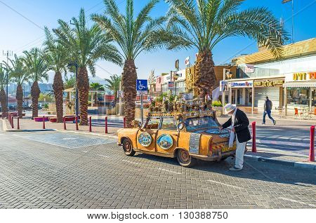 EILAT ISRAEL - FEBRUARY 24 2016: The tourist car driver cleans it of dust in the shopping neighborhood on February 24 in Eilat.