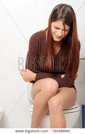 Young beautiful woman with stomache issues in bathroom