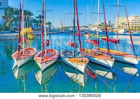 EILAT ISRAEL - FEBRUARY 23 2016: The sailing yachts in bright sun beams with the clear reflection in water on February 23 in Eilat.