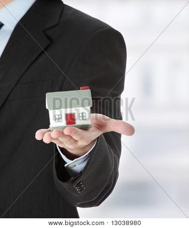Junger Geschäftsmann mit Haus-Modell auf Hand - Immobilien-Konzept.