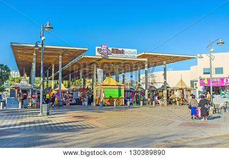 EILAT ISRAEL - FEBRUARY 23 2016: The central bazaar with many tourist souvenirs and beach accessories located on promenade on February 23 in Eilat.