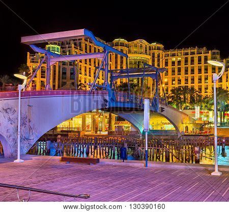 EILAT ISRAEL - FEBRUARY 24 2016: The evening view of the Memorial drawbridge and the luxury hotel in bright evening lights on February 24 in Eilat.
