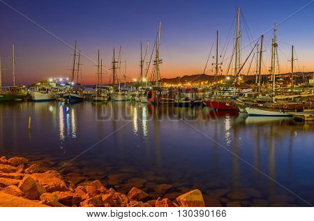 EILAT ISRAEL - FEBRUARY 24 2016: The nice view of the evening port full of yachts and boats with the red twilight sky on the background on February 24 in Eilat.