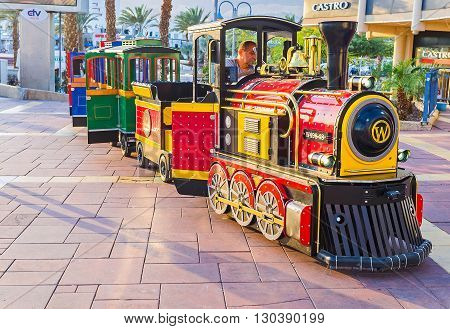 EILAT ISRAEL - FEBRUARY 23 2016: The colorful tourist train offers the pleasure rides along the promenade on February 23 in Eilat.