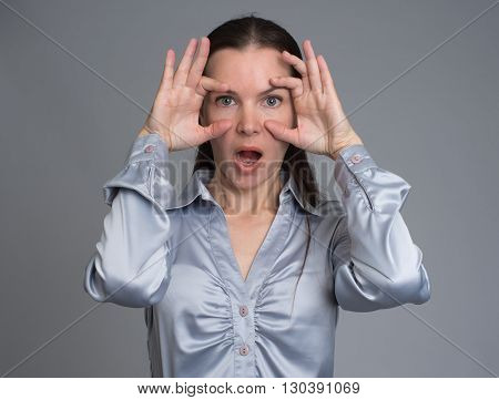 Surprised Young Brunette Woman. Grey Background