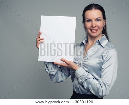Cheerful Brunette Woman Holding A White Blank Poster