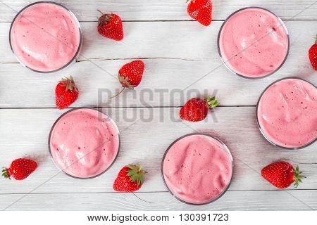 Strawberry Banana Smoothies Cups on an old white rustic wooden table with studio lights top view