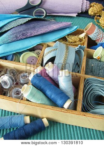 Wooden box with many blue sewing utensils