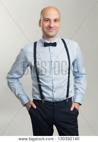 Fashionable Handsome Bald Man In Suspenders And Butterfly Tie