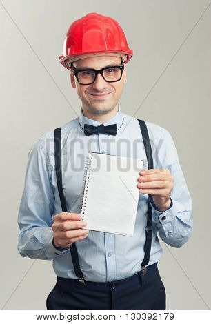 Business Man In A Helmet Shows The Blank Sheet Of Notepad