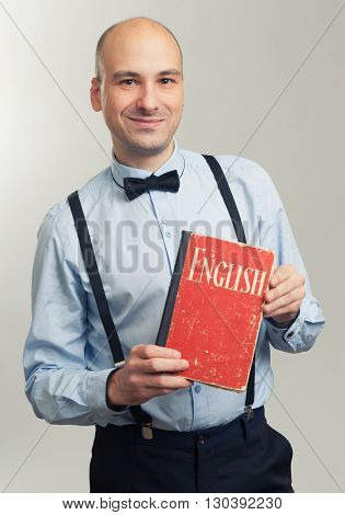 Stylish Bald Man Holding An English Textbook