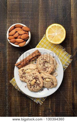 Almond cookies and almonds on white plate top view