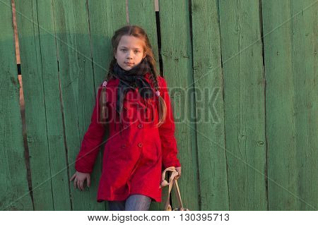 fashion girl in red raincoat posing near old wooden fence by evening