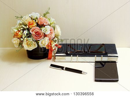 Artificial flowers and set of a black notebook glasses pen and smartphone on wood table blackground.