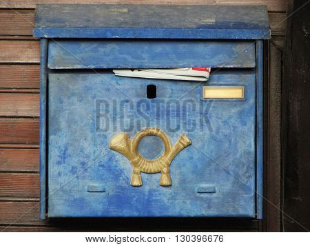 Blue mailbox on a brown wood wall