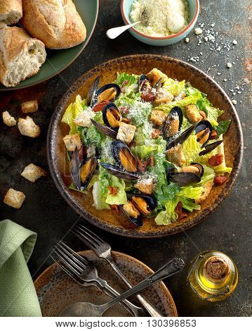 A delicious caesar salad with mussels romaine lettuce bacon croutons and parmesan cheese.