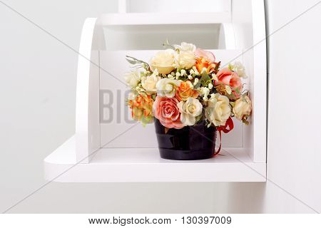 Artificial flowers in flowerpot on white wooden shelves.