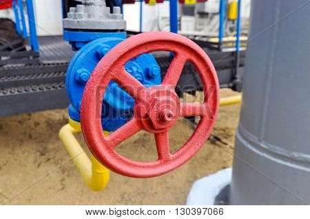 Red faucet with steel pipe in natural gas compressor station in summer day