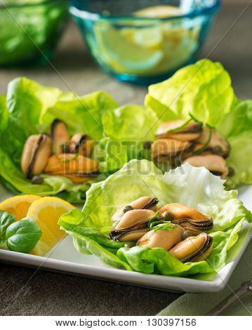 Delicious marinated mussels with capers lemon and basil on lettuce wraps.