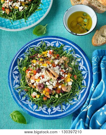 A delicious mediterranean mussel salad with chopped spinach red pepper yellow pepper cucumber kalamata olives and feta cheese.