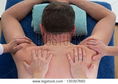 Man Getting Shoulder Massage By 2 Women