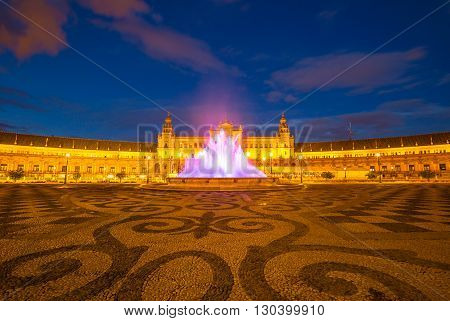 The spectacular and illuminated Square of Spain in Spanish Plaza de Espana, at night with its famous fountain and central building, Seville, Andalucia, Spain.
