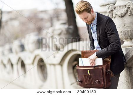 Young redhair businessman standing on the street