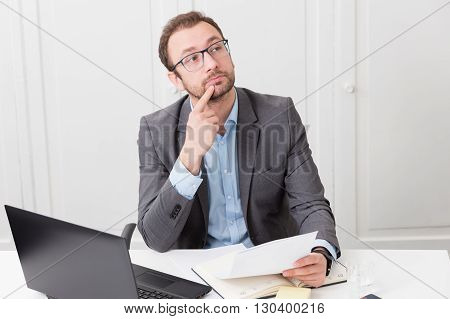 Pensive businessman at the desk in the office