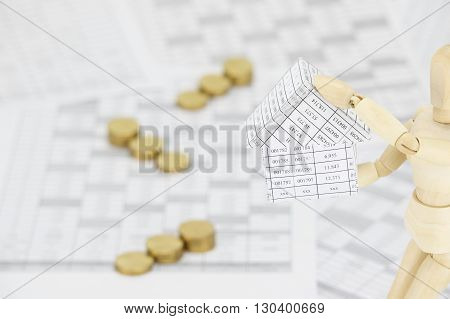 Wooden Dummy Holding House Have Blur Gold Coins As Background