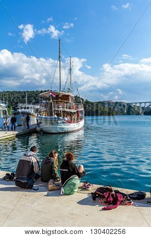 Skradin Croatia - May 05 2016: young people sitting on the edge of a dock