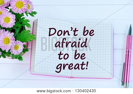The words Don't be afraid to be great on notebook