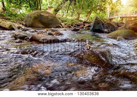Mountain stream in green forest in sun rays. Khao Sok National Park Surat Thani Province Thailand. Selective focus on a large rock in the foreground.