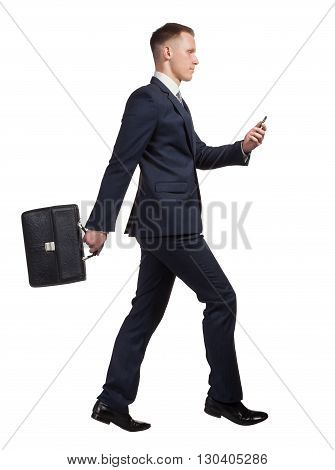 side view of jumping businessman with his briefcase, watching on the mobile phone on white background