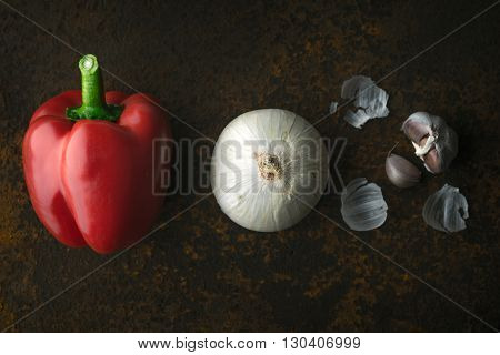 Red pepper white onion and garlic on a metal background horizontal