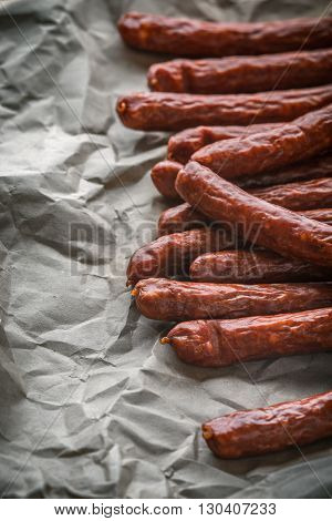 Many smoked sausage Chorizo on a background of paper vertical