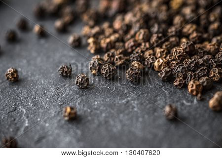 Large black pepper peas on black stone horizontal