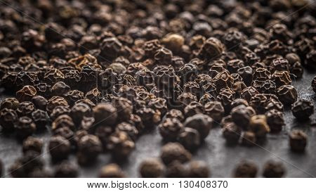 Many pea of black pepper on a gray slate horizontal