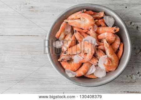 Shrimp and ice in the aluminum bowl on white boards horizontal